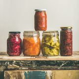Autumn seasonal pickled or fermented colorful vegetables, square crop. Autumn seasonal pickled or fermented colorful vegetables in jars over vintage kitchen stock photography