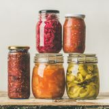 Autumn seasonal pickled or fermented vegetables. Home food canning concept. Autumn seasonal pickled or fermented colorful vegetables in glass jars placed in royalty free stock image