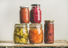 Autumn seasonal pickled or fermented vegetables. Home food preserving. Autumn seasonal pickled or fermented colorful vegetables in glass jars placed in stack Stock Image