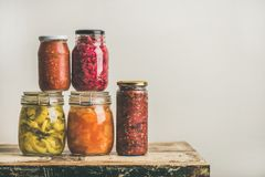 Autumn seasonal pickled or fermented vegetables in jars, copy space. Autumn seasonal pickled or fermented colorful vegetables in glass jars placed in stack over royalty free stock images