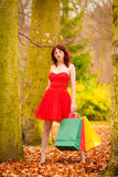 Autumn shopper woman with sale bags outdoor in park Royalty Free Stock Photos