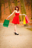 Autumn shopper woman with sale bags outdoor in park Stock Photo
