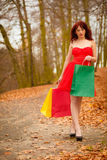 Autumn shopper woman with sale bags outdoor in park Royalty Free Stock Photo