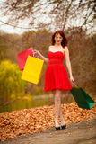 Autumn shopper woman with sale bags outdoor in park Royalty Free Stock Photography