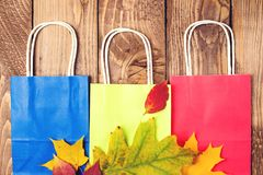 Autumn shopping. Fallen leaves on paper bags. Flat lay. Autumn sales. Shopping bags on wooden background. Autumn fashion. Shopping royalty free stock photos