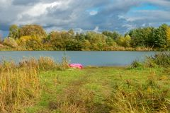 In the autumn on the shore of the lake. Autumn landscape. The shore of a small lake in sunny autumn day Stock Photos