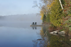 Autumn Shoreline and Dock on a Misty Morning. In the Haliburton Highlands - Ontario, Canada royalty free stock photo