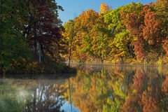 Autumn, Shoreline Eagle Lake. Autumn shoreline of Eagle Lake with fog with reflections in calm water, Fort Custer State Park, Michigan, USA Royalty Free Stock Image