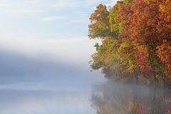 Autumn Shoreline in Fog. Autumn shoreline of Eagle Lake in fog with reflections in calm water, Fort Custer State Park, Michigan, USA Royalty Free Stock Image