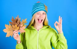 Autumn skincare tips. Active leisure and rest autumn season. Bright moment. Woman wear knitted hat hold fallen leaves
