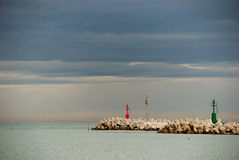 Autumn sky at harbour entrance. Red and green lighthouses point out the way in of the harbour in a cloudy autumn day Royalty Free Stock Photo