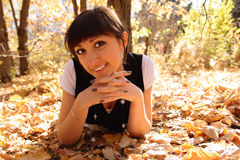 Autumn smile. Beautiful young woman lays on autumn leaves Stock Image