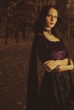 Autumn sorrow. Pretty gothic girl in purple dress standing in the park Stock Photos