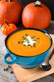 Autumn soup in blue bowl with pumpkins in background Royalty Free Stock Photos