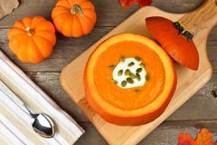 Autumn soup topped with seeds and cream in pumpkin bowl Stock Images
