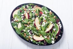 Autumn spinach salad with apple cheese , walnut and dried cranberry . Healthy vegetarian food. Autumn spinach salad with apple , cheese , walnut and dried stock images