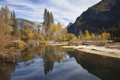 Autumn splendor in Yosemite. Half Dome is reflected in the calm waters of Merced River amid bright fall colors in Yosemite Valley, Sierra Nevada, California Royalty Free Stock Photo