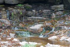Autumn spring. Water flowing over rocks with autumn leaves Royalty Free Stock Images