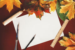Autumn stationery set. Fallen maple leaves and stationery items Royalty Free Stock Photos