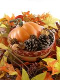 Autumn Still Life. Arrangement of silk autumn leaves, pine cones and a little pumpkin Stock Images