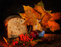 Autumn still life. Of yellow leaves, ripe mountain ash with apple and bread Royalty Free Stock Photos