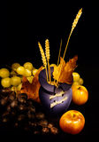 Autumn still life. Autumn fruits (grapes and apples) surrounding blue vase; photographed in the dark and on black background Royalty Free Stock Images
