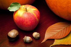 Autumn Still Life 3. Two pumpkins, an apple, a chestnut, acorns and autumn leaves on a warm wooden tabletop Royalty Free Stock Images