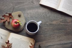 Autumn still life with apple, coffee, open books and leaves over rustic wooden background, copy space, horizontal, aerial view. Autumn season still life with royalty free stock images
