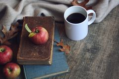 Autumn still life with apples, warm blanket, books and leaves over rustic wood background. Stock Photography