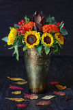 Autumn still life. Autumn bouquet of flowers with sunflowers and leaves on a dark wooden background Stock Image