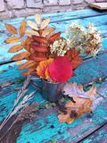Autumn still life: bouquet of flowers and autumn leaves in a steel mug. Bouquet of flowers and autumn leaves in a steel mug on a old wooden green background Stock Image