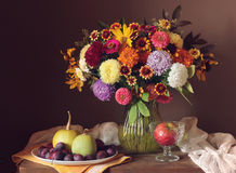 Autumn still life with bouquet and fruits. Stock Photography