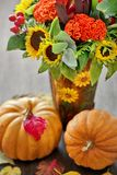 Autumn still life. Autumn bouquet with pumpkins ,sunflowers and leaves on a wooden background Stock Photography