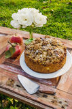 Autumn still life with cake, walnuts, apples and white roses. Rustic style. Royalty Free Stock Image