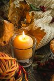 Autumn still life. With candle, sweater and oak leaves Stock Image