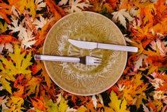 Autumn Still Life con una placa, un cuchillo y una bifurcación para la cena en un fondo de hojas Foto de archivo