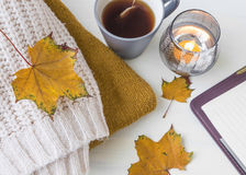 Autumn still life cozy items with woolen sweaters, candle, tea a Royalty Free Stock Image