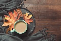 Autumn still life with cup of coffee, colorful dry leaves warm scarf on wooden board. Copy space. Top view. Autumn still life with cup of coffee, colorful dry royalty free stock image
