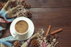 Autumn still life with cup of coffee,cone, cinnamon, warm scarf on wooden board. Copy space. Top view. Autumn still life with cup of black coffee, cone royalty free stock photo