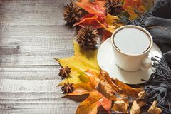 Autumn still life with cup of coffee,cone, cinnamon, warm scarf on wooden board. Copy space. Top view. Autumn still life with cup of black coffee, cone royalty free stock photography