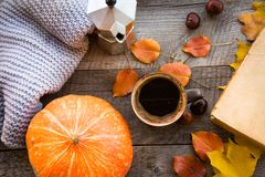 Autumn still life. Cup of coffee, warm scarf and pumpkin on wooden board. Top view, vintage style. Royalty Free Stock Photos