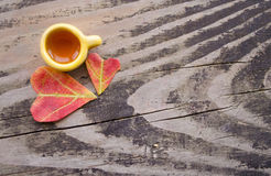 Autumn still-life. A cup of warm drink and two leaves in the shape of hearts on a gray wooden background Stock Photos