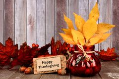 Autumn still life with Happy Thanksgiving tag, leaves and decor Stock Images