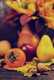 Autumn still life of harvest and walnuts lying on tree leaf on w. Ooden desk. Mockup for seasonal offers and holiday post card Royalty Free Stock Photo