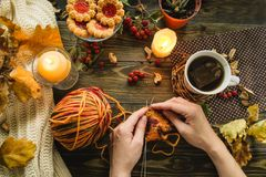 Autumn knitting of still life. Autumn still life with knitting, candle, sweater and oak leaves Royalty Free Stock Photo