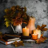 Autumn still life. Lit candles, bouquet of maple leaves, books, pumpkin on a gray background