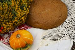 Autumn still life - loaf, pumpkin, mountain ash, tansy, wheat ears, salt,on a white tablecloth with lace Stock Photo