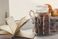 Autumn still-life, nuts, citrus fruits and book Royalty Free Stock Images