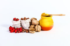 Autumn still life of nuts, wild rose pot of honey isolated on wh Stock Photos