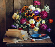Autumn still life with open book and a bouquet of flowers Royalty Free Stock Images